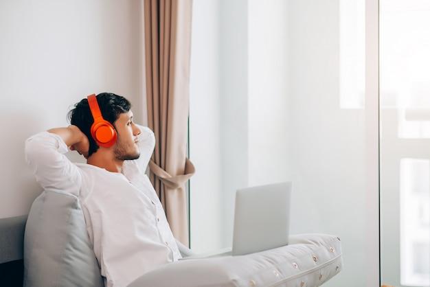 Giovane uomo asiatico che si rilassa a casa mentre indossando la cuffia avricolare stereo alla musica d'ascolto al salone