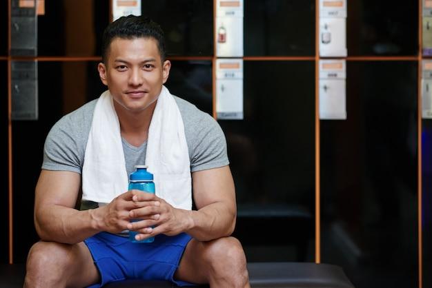 Giovane uomo asiatico che si siede nello spogliatoio in palestra con la bottiglia di acqua e l'asciugamano