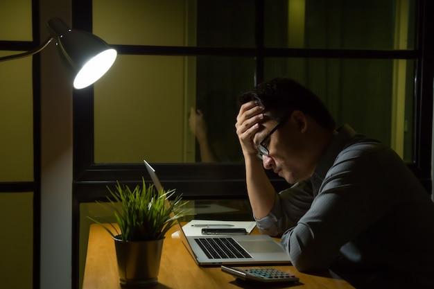 Giovane uomo asiatico che si siede sulla tavola dello scrittorio che esamina computer portatile nel pensiero a tarda notte scuro che ritiene pensiero serio e sforzo all'ufficio. lavoro straordinario e duro lavoro