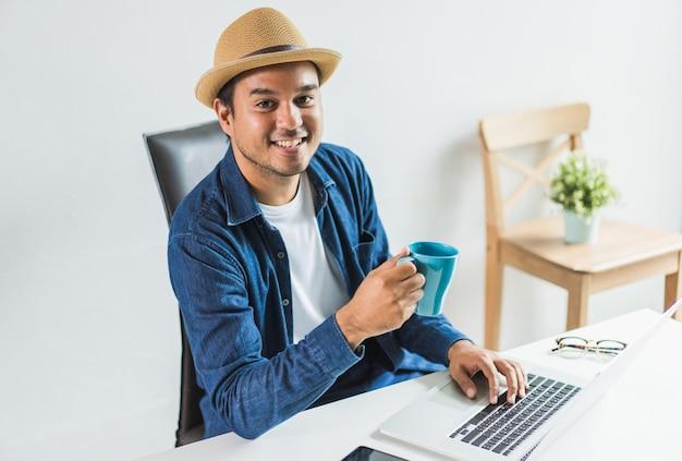 Giovane uomo asiatico che tiene e beve una tazza di caffè al mattino