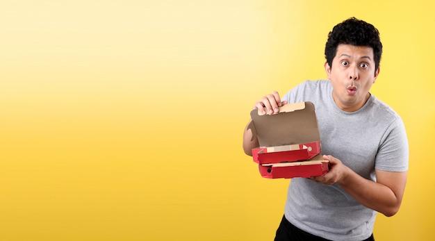Giovane uomo asiatico che tiene la scatola di consegna con pizza italiana spaventato per lo shock con una faccia sorpresa,