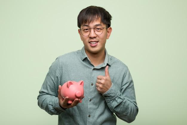 Giovane uomo asiatico che tiene un porcellino salvadanaio che sorride e che alza pollice in su