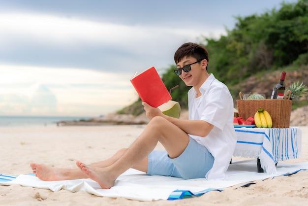 Giovane uomo asiatico con gli occhiali da sole che legge sulla spiaggia