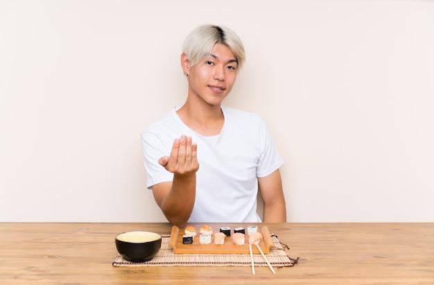 Giovane uomo asiatico con i sushi in una tabella che invita a venire