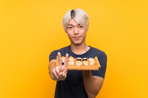 Giovane uomo asiatico con i sushi sopra giallo isolato che sorride e che mostra il segno di vittoria