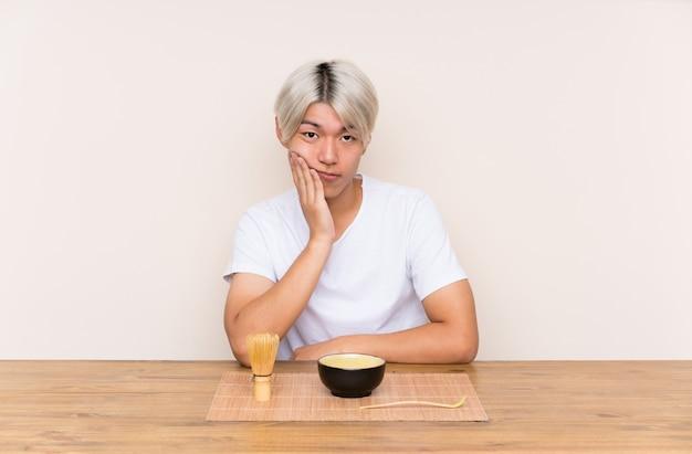 Giovane uomo asiatico con il tè di matcha in una tabella infelice e frustrata