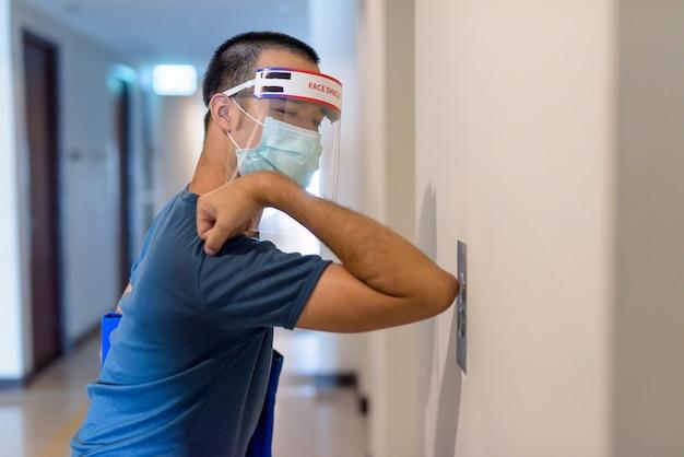 Giovane uomo asiatico con maschera e visiera che preme il pulsante dell'ascensore con il gomito per prevenire la diffusione del coronavirus