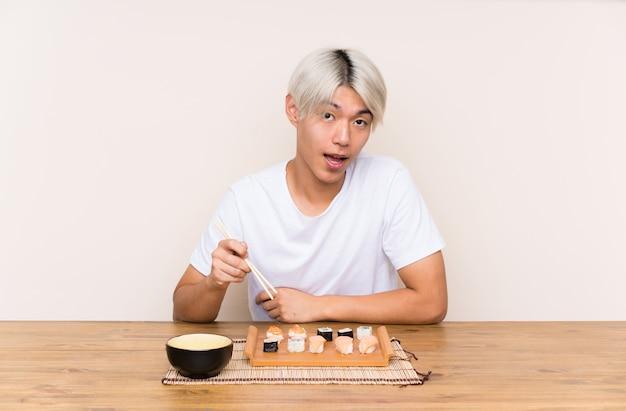 Giovane uomo asiatico con sushi in una tabella