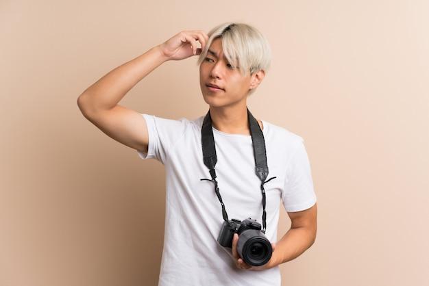 Giovane uomo asiatico con una macchina fotografica e un pensiero professionali