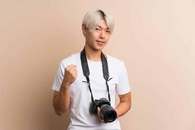 Giovane uomo asiatico con una macchina fotografica professionale e con il pollice in su