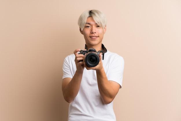 Giovane uomo asiatico con una macchina fotografica professionale