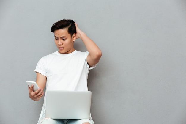 Giovane uomo asiatico confuso che esamina telefono cellulare.