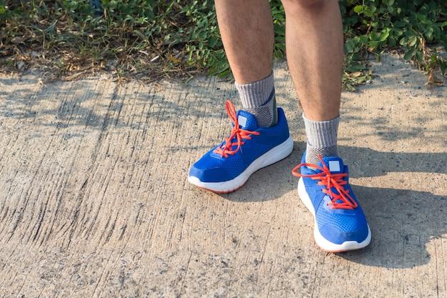 Giovane uomo asiatico dell'atleta che lega le scarpe da corsa nella casa anteriore, corridore maschio pronto per fare jogging