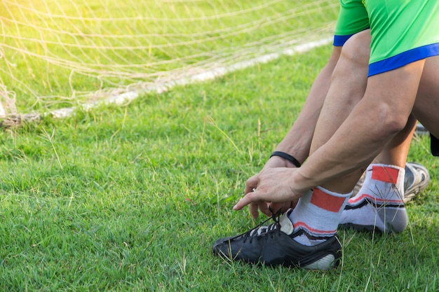 Giovane uomo asiatico dell'atleta che lega le scarpe di calcio al lato del campo