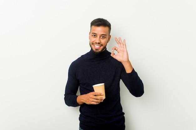 Giovane uomo asiatico di razza mista che tiene un gesto da asporto allegro e fiducioso mostrando un caffè da asporto