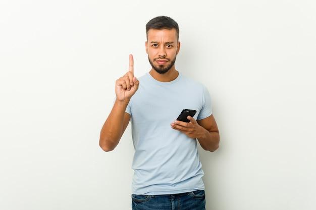 Giovane uomo asiatico di razza mista che tiene un telefono che mostra il numero uno con il dito.
