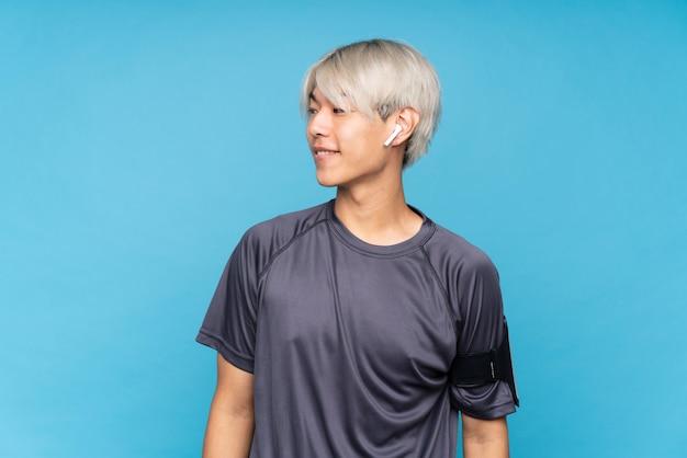 Giovane uomo asiatico di sport sopra il lato di sguardo blu isolato