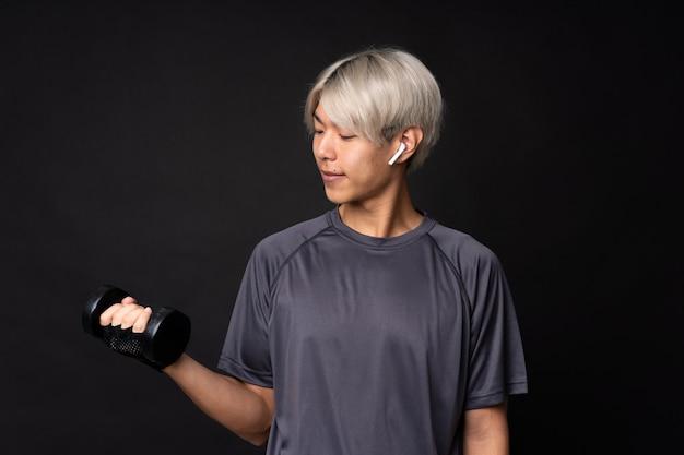 Giovane uomo asiatico di sport sopra il nero isolato