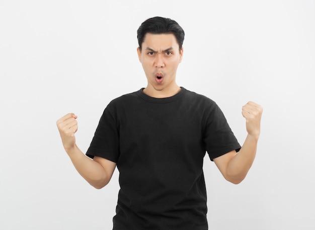 Giovane uomo asiatico emozionante che alza i pugni con il fronte felice felice, celebrante successo