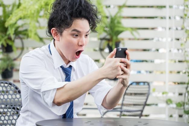 Giovane uomo asiatico emozionante di affari che celebra successo
