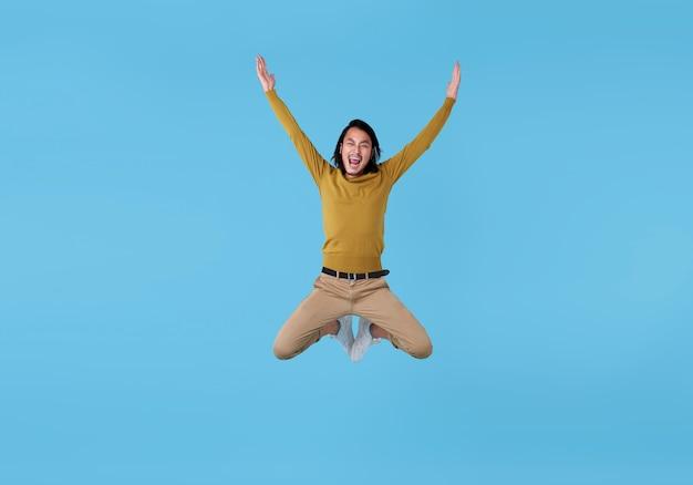 Giovane uomo asiatico energico felice che salta a mezz'aria isolato su spazio blu.