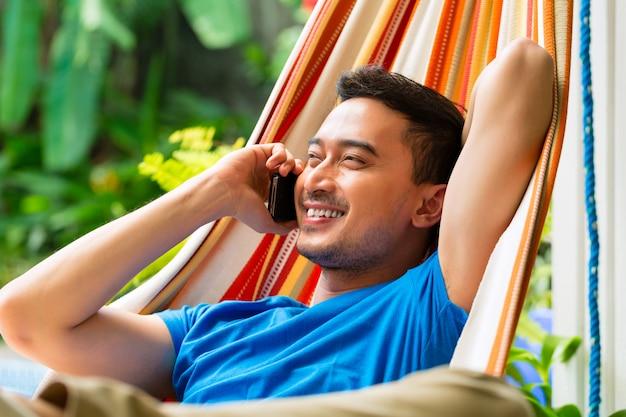 Giovane uomo asiatico in amaca con il telefono