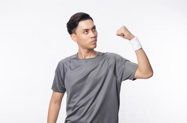 Giovane uomo asiatico in attrezzature sportive che mostrano forza e guardando al copyspace isolato sulla parete bianca