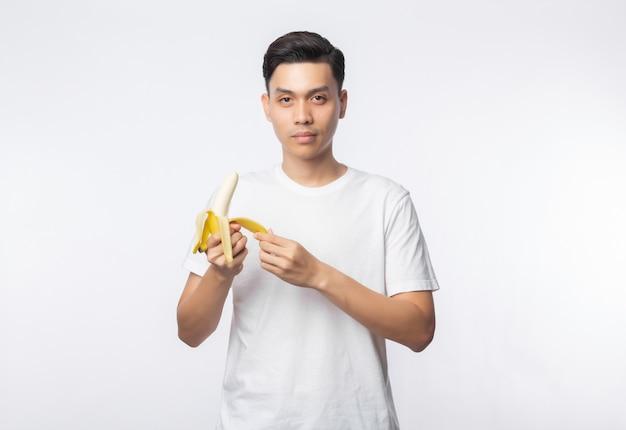 Giovane uomo asiatico in banana bianca della sbucciatura della maglietta e guardare alla macchina fotografica isolata sulla parete bianca