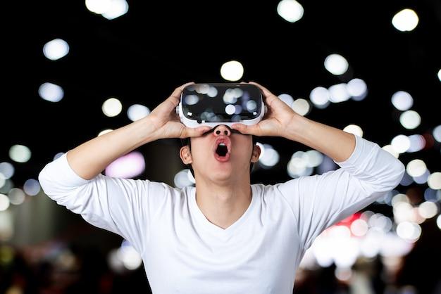 Giovane uomo asiatico in bianco casuale che indossa e che tiene i vetri di vr a mano cercando sopra