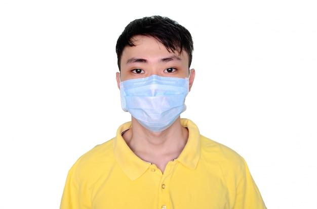 Giovane uomo asiatico in maglietta gialla che indossa maschera medica, isolato su sfondo bianco. coronavirus o concetto di protezione covid-19.