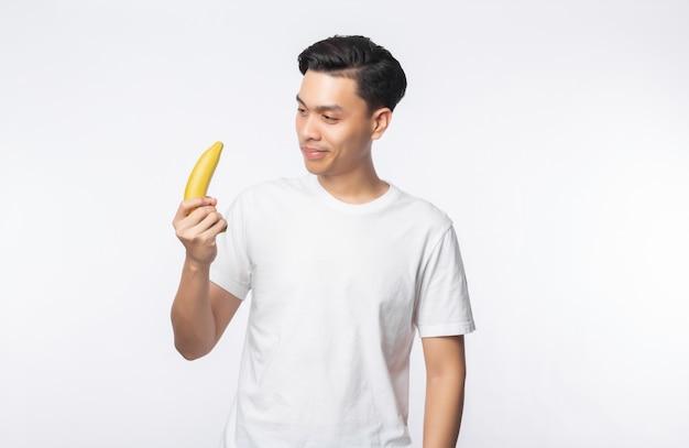 Giovane uomo asiatico nella banana bianca della tenuta della maglietta con il fronte felice isolato sulla parete bianca