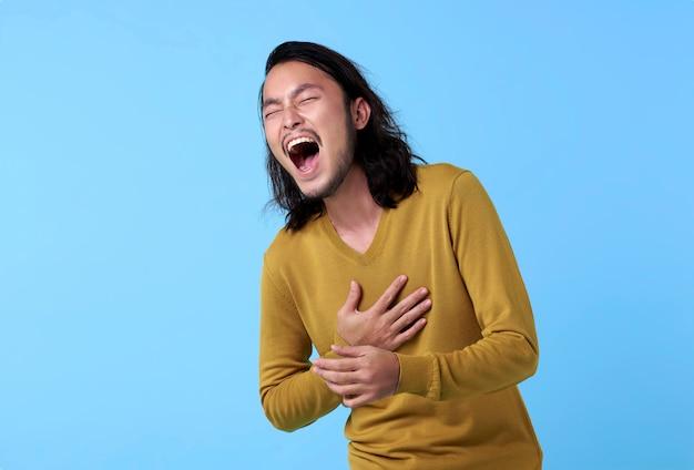 Giovane uomo asiatico soddisfatto del fronte di risata su spazio blu.
