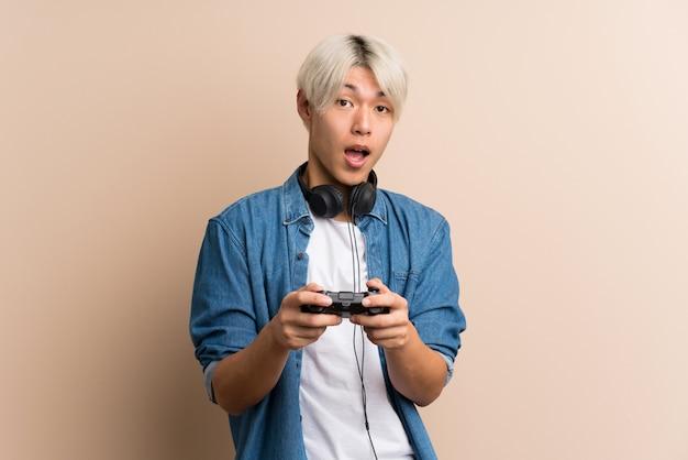 Giovane uomo asiatico sopra giocando isolato ai videogiochi