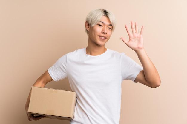 Giovane uomo asiatico sopra isolato in possesso di una scatola per spostarlo in un altro sito e salutare