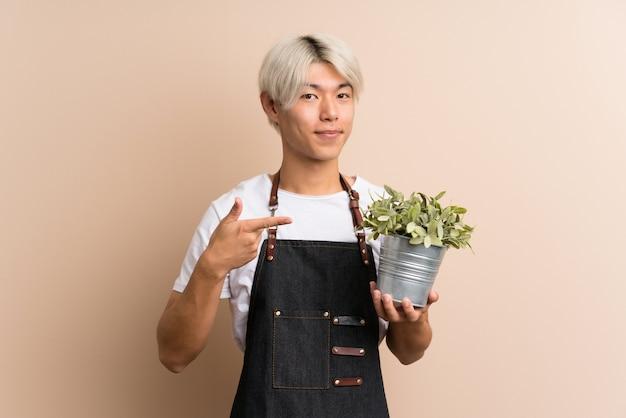 Giovane uomo asiatico sopra isolato prendendo un vaso di fiori e indicandolo