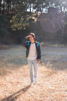 Giovane uomo asiatico sorridente che cammina nel parco