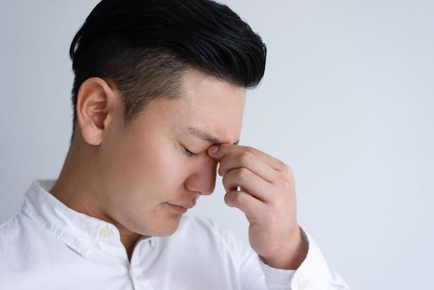 Giovane uomo asiatico stanco che tocca il suo ponte del naso