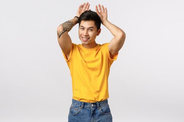 Giovane uomo asiatico tatuato sciocco e carino in maglietta gialla, imitando il coniglietto, mostrando le orecchie di coniglio con le mani sulla testa, sorridendo gioioso, in piedi sciocco, scherzando, in piedi muro bianco