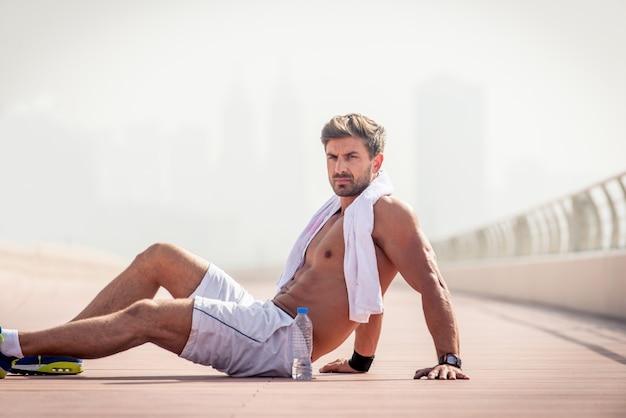 Giovane uomo atletico al piano strada