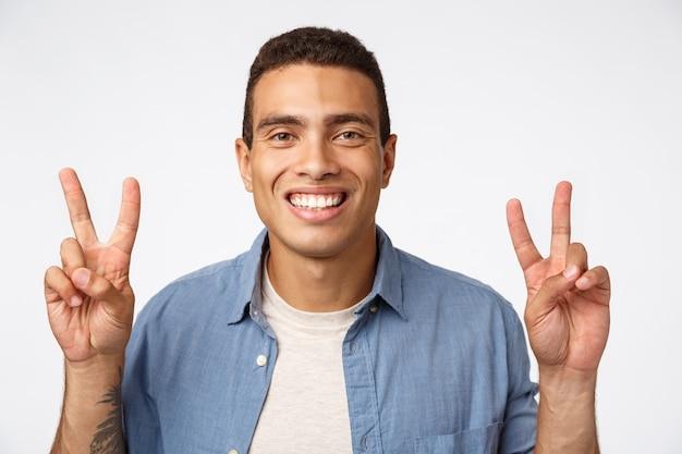 Giovane uomo atletico allegro in attrezzatura casuale che sorride felicemente, mostrando i segni di pace o la citazione