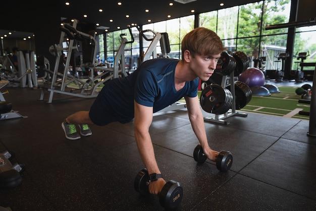 Giovane uomo atletico che risolve con i pesi di dumbbell al club di sport della palestra