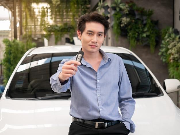 Giovane uomo attraente asiatico che sta vicino ad un'automobile al concessionario e che mostra le chiavi dell'automobile.