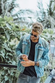 Giovane uomo attraente che propone in una posizione tropicale, su uno sfondo di palme e verde
