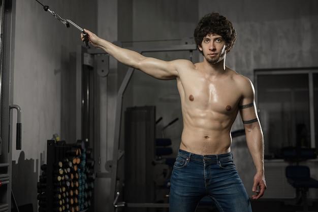 Giovane uomo attraente che riposa in palestra dopo l'esercizio, posa maschile