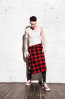 Giovane uomo attraente che sta sulla posa del pavimento