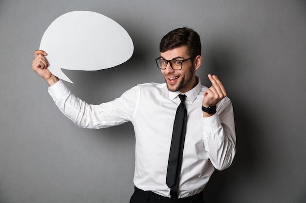 Giovane uomo attraente in camicia bianca che tiene la bolla vuota del messaggio,