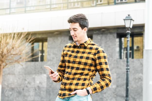 Giovane uomo attraente in camicia gialla usando uno smartphone davanti all'edificio