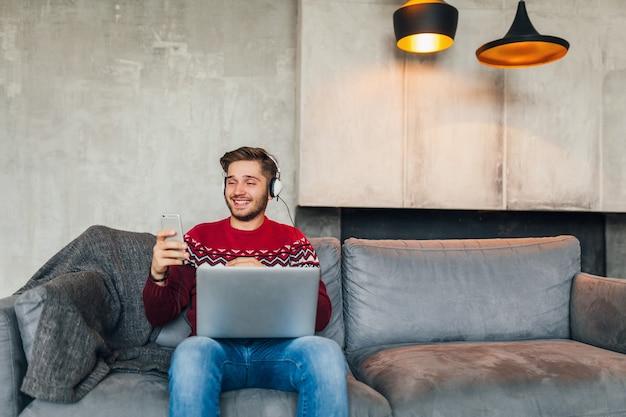 Giovane uomo attraente sul divano di casa in inverno con lo smartphone in cuffia, ascolto di musica, indossa un maglione lavorato a maglia rosso, lavora al computer portatile, libero professionista, sorridente, felice, positivo, digitando