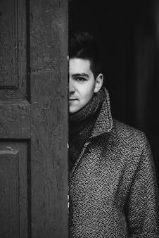 Giovane uomo attraverso la vecchia porta di legno