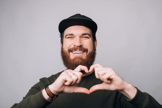 Giovane uomo barbuto allegro che mostra il gsture del cuore con entrambe le mani.